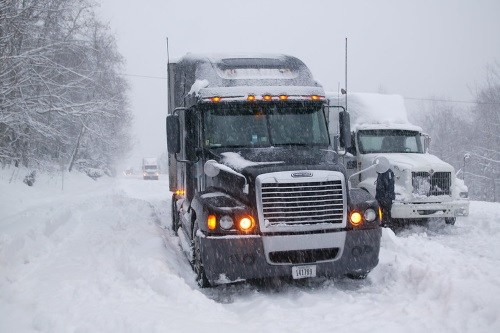 Trucks in snow illustrating highway freight transportation.