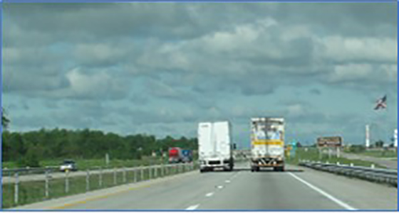 Image of highway, trailers, and sky.