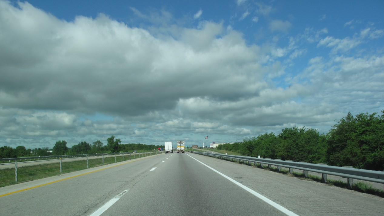 Highway image showing the back end of two tractor trailers traveling on the highway.